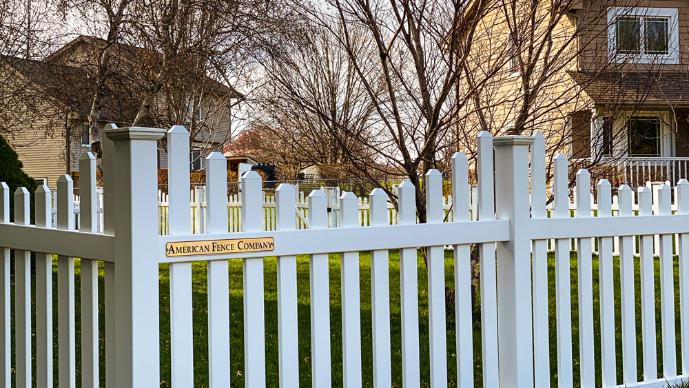 White vinyl under scalloped picket fence on residential property. Madison fence contractors fencing company Wisconsin overscalloped arched picket plank vinyl wood cedar western red cedar alternating board on board cap red cedar white khaki chestnut sandstone tan UVB sun solid french scalloped